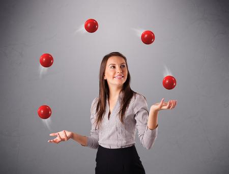 mooie jonge meisje staan en jongleren met rode ballen
