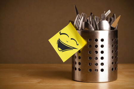 case sheet: Drawn smiley face on a  note sticked on a cutlery case Stock Photo