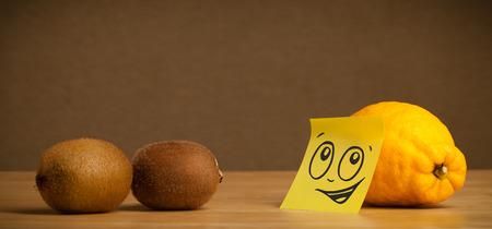 reacting: Lemon with sticky  note reacting on kiwis