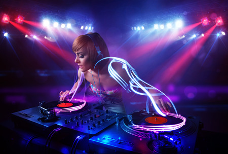 Pretty young disc jockey girl playing music with light beam effects on stage photo