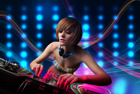 Beautiful young Dj girl mixing records with colorful lights photo