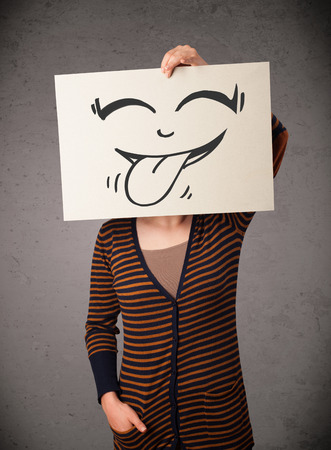 hiding face: Young woman holding a paper with a cute smiley face on it in front of her head