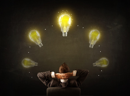Young businessman sitting in office chair in front of a balckboard with glowing lightbulbs over his head photo