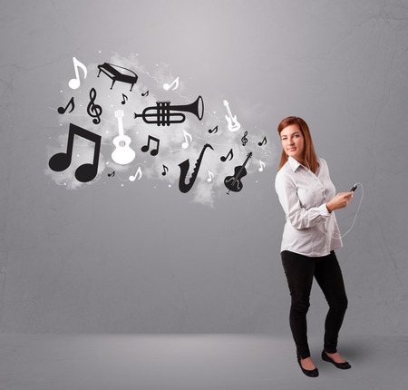 Beautiful young woman singing and listening to music with musical notes and instruments getting out of her mouth photo