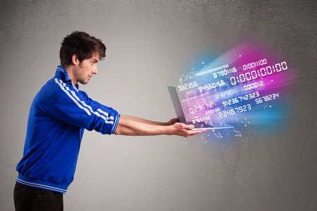 to encode: Casual young man holding laptop with exploding data and numbers Stock Photo