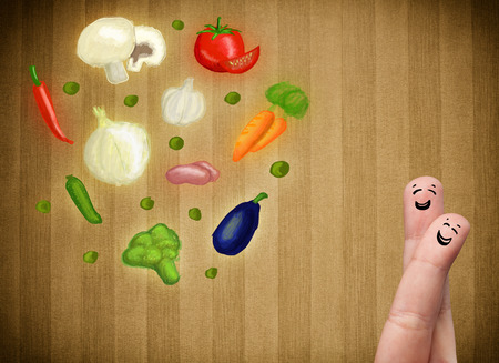 Happy smiley face fingers cheerfully looking at illustration of colorful healthy vegetables Stock Photo