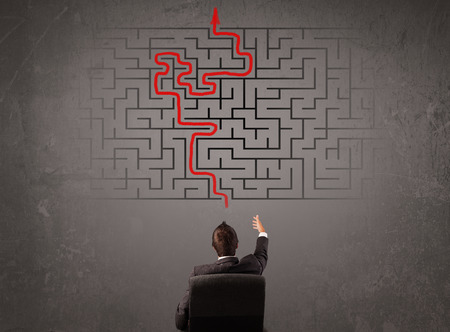 Business man looking at a maze and the way out on brown wall Stock Photo