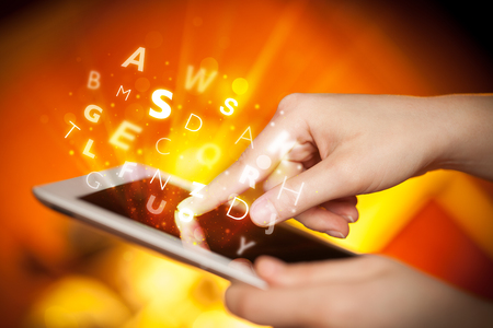 tablet pc in hand: Hand touching tablet pc, letters concept