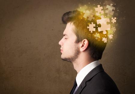 persona pensando: Persona joven que piensa con la mente del rompecabezas que brilla intensamente en fondo sucio