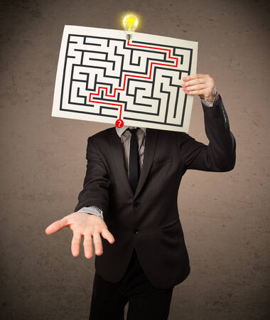 Young businessman holding a paper with a labyrinth on it in front of his head photo