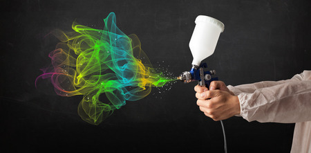 paint gun: Painter working with airbrush and paints colorful paint concept