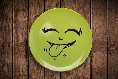 emotions faces: Happy smiley cartoon face on colorful dish plate and grungy background