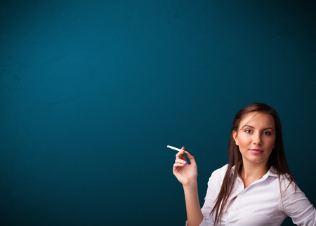 Beautiful young woman smoking cigarette with copy space photo