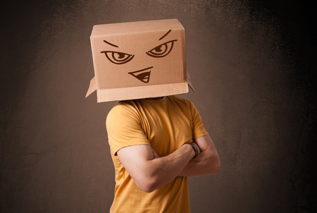 cardboard box: Young man standing and gesturing with a cardboard box on his head with evil face