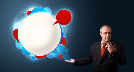 businessman in suit making phone call and presenting abstract modern speech bubble with copy space photo