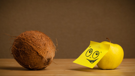 reacting: Apple with sticky post-it note reacting to coconut