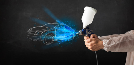 paint gun: Worker with airbrush gun painting hand drawn white car lines Stock Photo