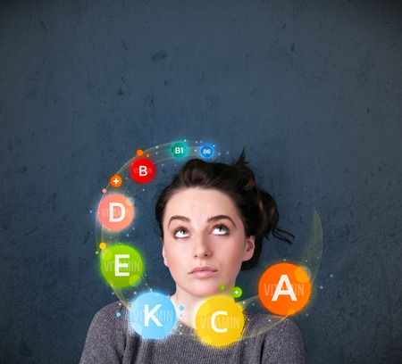Thoughtful young woman with vitamin icons circulating around her head photo