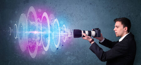 Young photographer making photos with powerful light beam photo