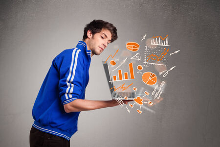 Handsome young man holding laptop with graphs and statistics photo