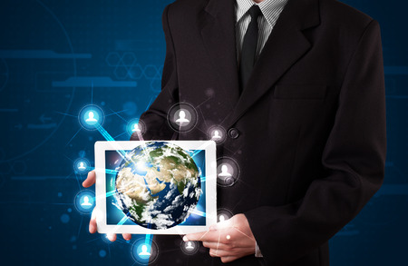 Young businessman presenting 3d earth globe in tablet photo