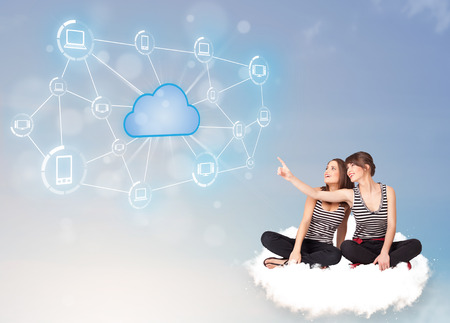 Happy young women sitting on clous with cloud computing photo
