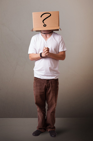 Young man standing and gesturing with a cardboard box on his head with question mark Stock Photo