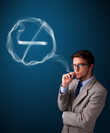 Handsome young man smoking unhealthy cigarette with no smoking sign photo