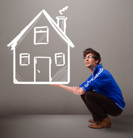dwelling: Attractive young boy holding a huge drawn house