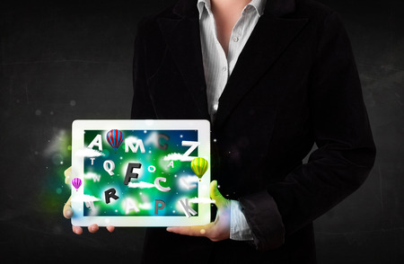 abstract letters: Young person showing white tablet with abstract letters and sky Stock Photo