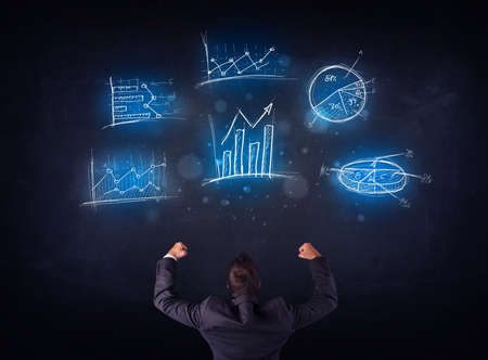 Young businessman standing in front of glowing charts and diagrams photo