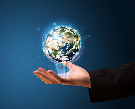 Young businessman holding in his hand a glowing earth globe. photo