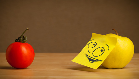 reacting: Apple with sticky note reacting at tomato Stock Photo