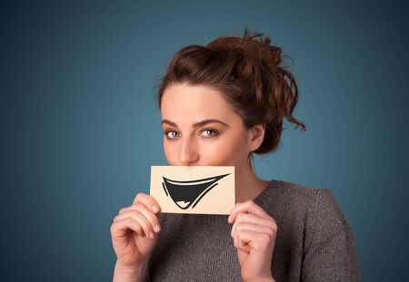 Happy cute girl holding paper with funny smiley drawing on gradient background photo