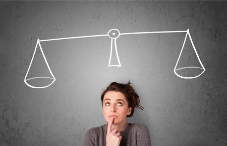 balanza en equilibrio: Señora bastante joven de tomar una decisión con la escala por encima de la cabeza