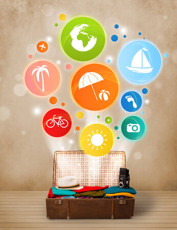 Suitcase with colorful summer icons and symbols on grungy background photo