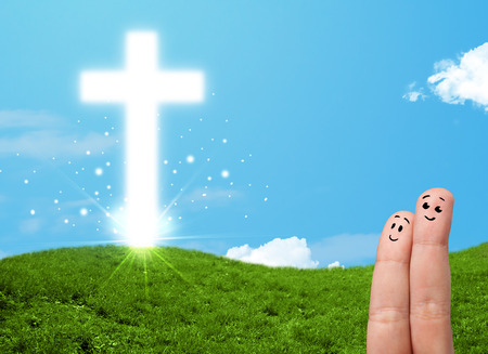 Happy finger smiley faces on hand with christian religion cross photo