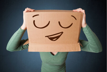 masquerader: Young woman standing and gesturing with a cardboard box on her head with smiley face Stock Photo