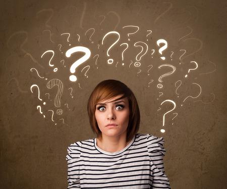 mujer reflexionando: Adolescente con símbolos de signo de interrogación alrededor de la cabeza
