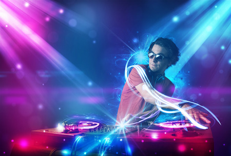 若いエネルギッシュな Dj の強力な光の効果と音楽をミキシング