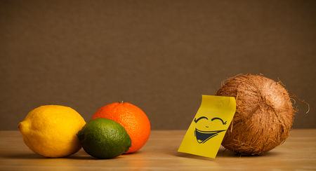 reacting: Coconut with sticky note reacting to citrus fruits Stock Photo