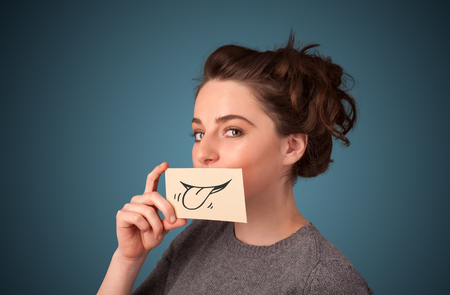 Pretty young girl holding white card with smile drawing on gradient background photo