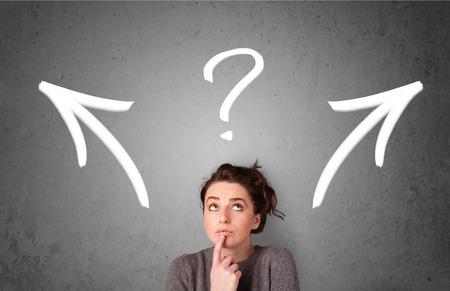 Piuttosto giovane donna di prendere una decisione con le frecce e il punto interrogativo sopra la sua testa Archivio Fotografico