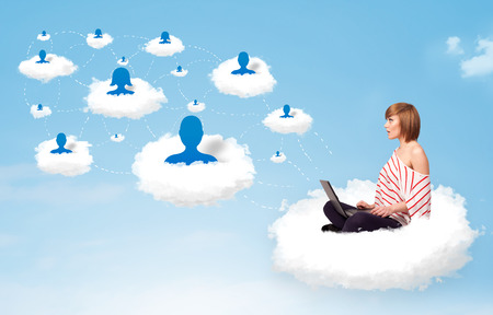Pretty young woman sitting in cloud with laptop, social network concept photo