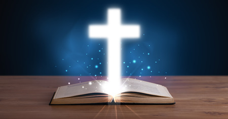 Open holy bible with glowing cross in the middle on wooden deck Stock Photo