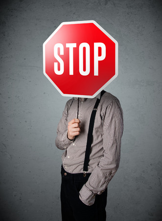 hidden success: Businessman standing and holding a stop sign in front of his head Stock Photo