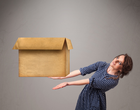 Beautiful young woman holding an empty cardboard box photo