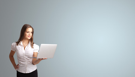 attractive young woman holding a laptop with copy space photo
