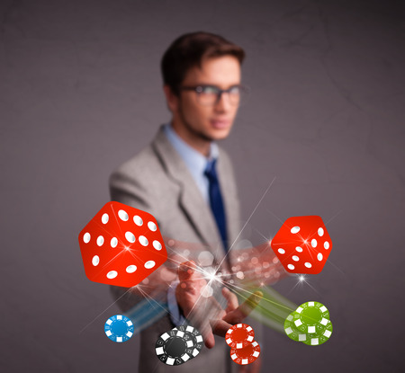 Attractive young man throwing dices and chips photo