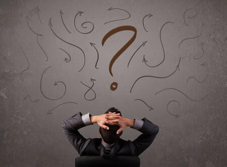 Business man looking at question mark sketch on the wall